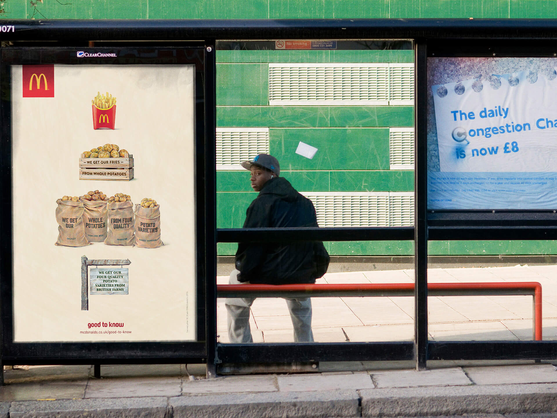 A teenage boy waits at a bus stop displaying a Congestion Charge poster on the Harrow Road West London
